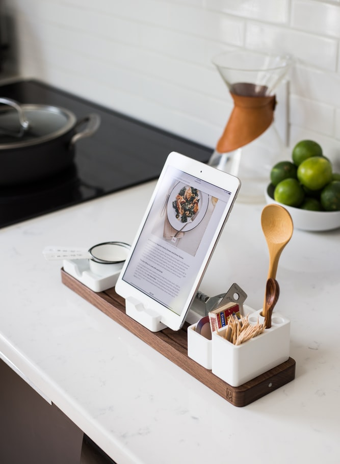 white ipad on a wooden tray stand in the kitchen